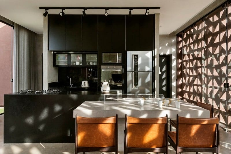 Black kitchen showcasing an interesting wall with geometric holes pattern.  It has a white marble breakfast island with leather counter chairs.