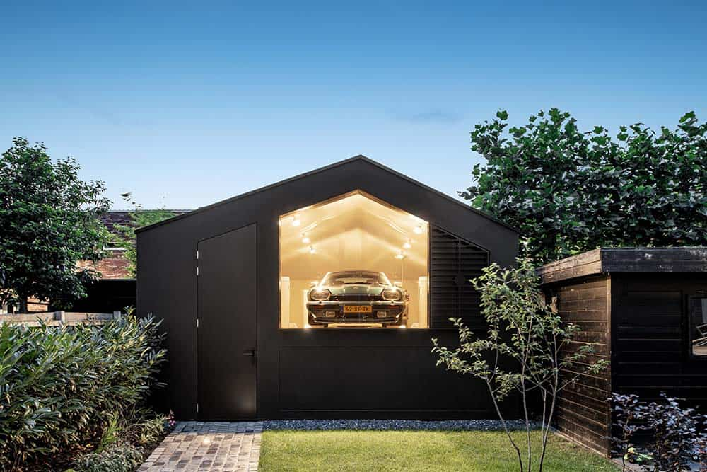 This is a close look at the house with a unique black contemporary design to it with a large glass wall that displays the car parked inside with warm glowing interiors complemented by a grass lawn.