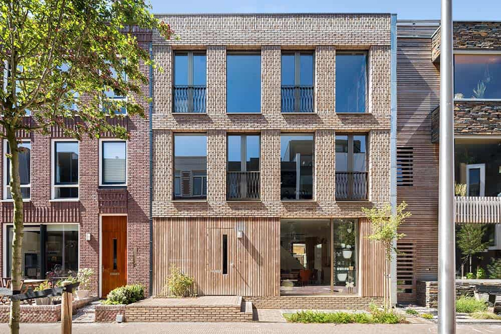 This is a close look at the front of the house that has red brick walls on its upper two floors and shiplap wooden walls and glass walls on the ground level adorned by simple landscaping.