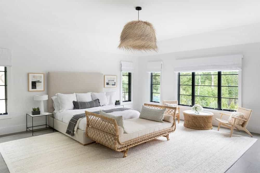 A spacious bedroom featuring hardwood floors, white walls and ceiling along with a large brown area rug.