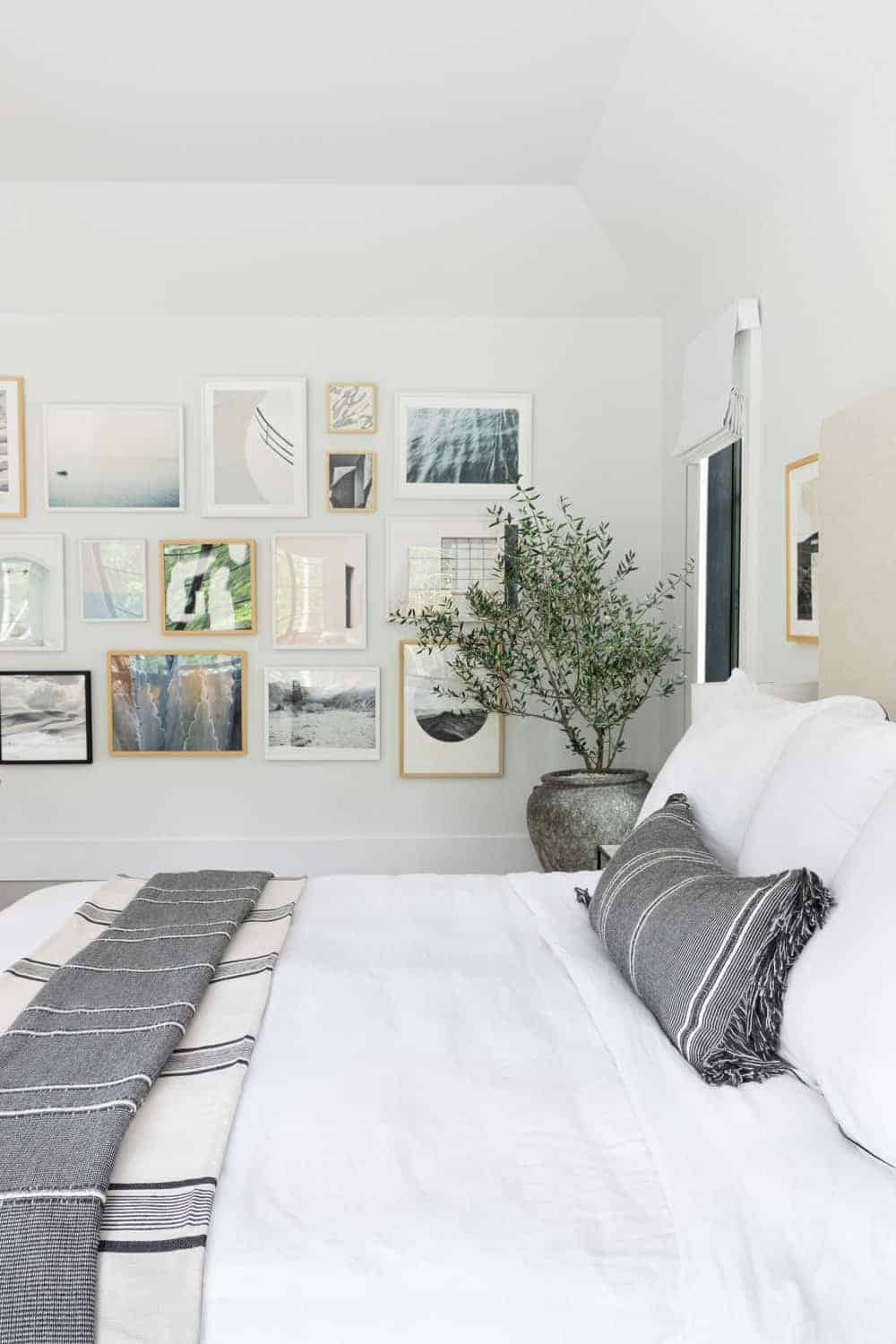 The master bedroom is surrounded by white walls and ceiling. The walls are decorated with multiple framed wall decors.