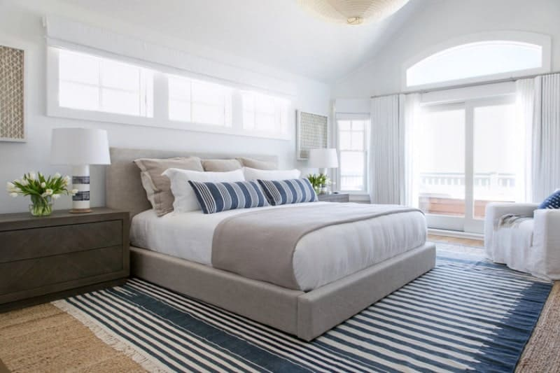Bright primary bedroom accented with a striking stripes rug matching the pillows. It has a gray bed frame and dark wood nightstands with white table lamps.