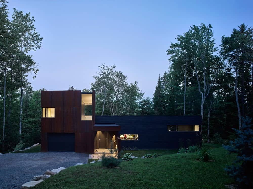 Classic contemporary house in blackened timber and weathering steel with towering trees behind and a beautiful sloped terrain covered with rock border.