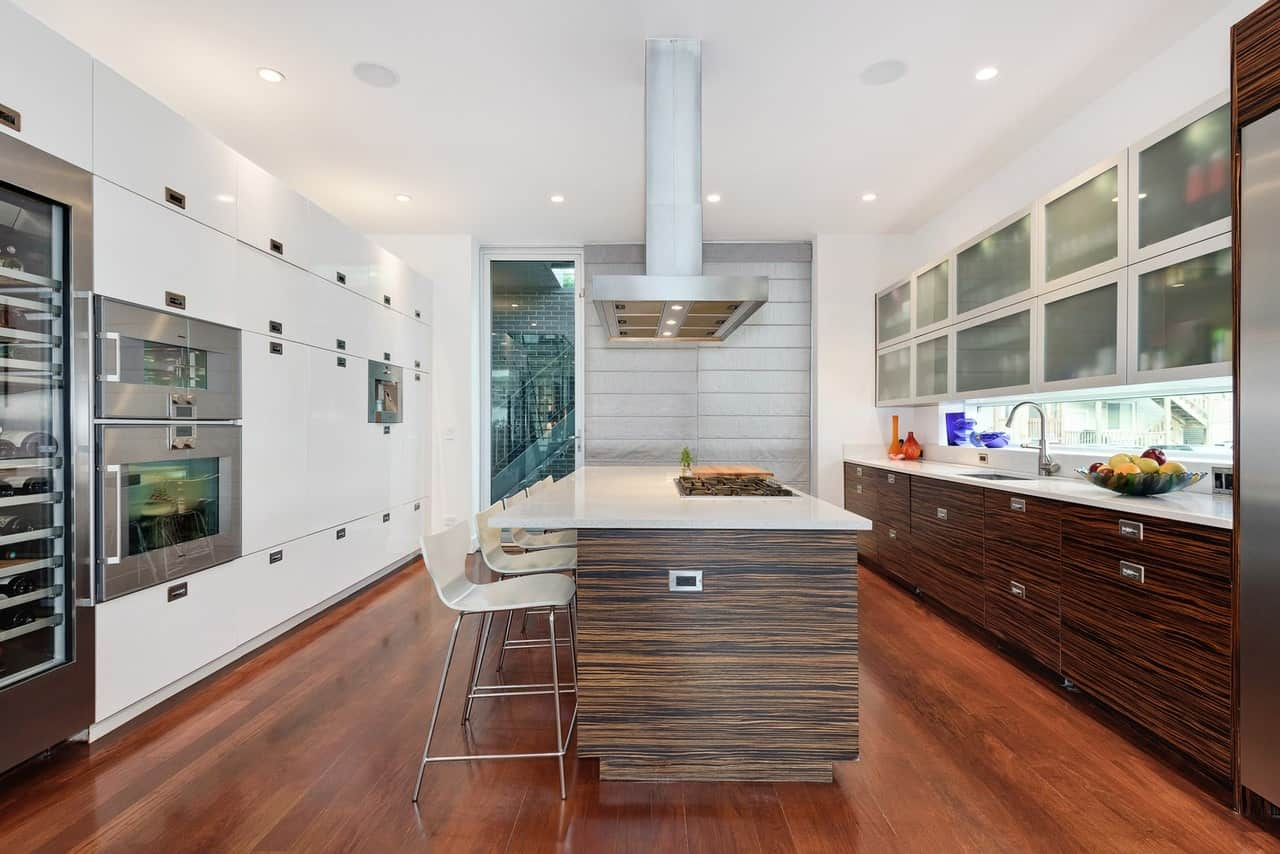 Modern galley kitchen boasts sleek white cabinetry on the left along with frosted front glass upper cabinetry and wooden lower cabinetry on the right. There's a vent hood in the center suspended over a wooden breakfast island with white chairs.