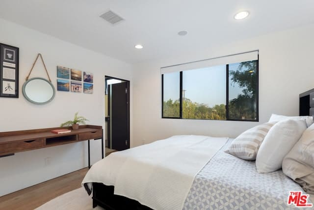White master bedroom with hints of black decorated with a round mirror mounted above a wooden desk.