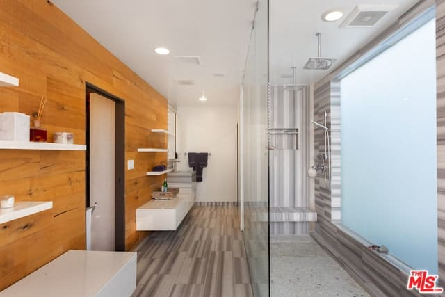 Walk-in shower area with frosted glass walls along with gray tiles and glass enclosure. The primary bathroom features floating shelves mounted on the wooden wall.