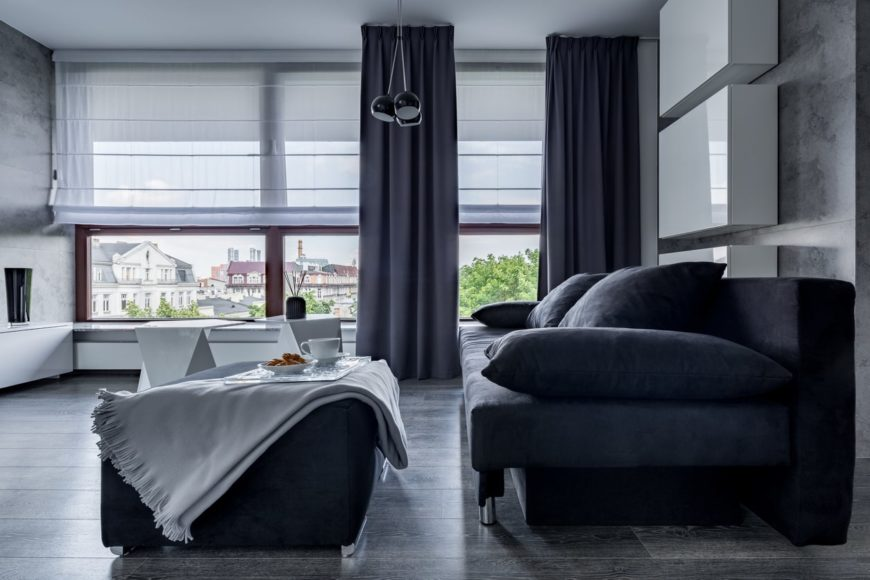 A black living room filled with a huge velvet sofa and ottoman. It has glass windows wrapped in translucent roman shades and black draperies.