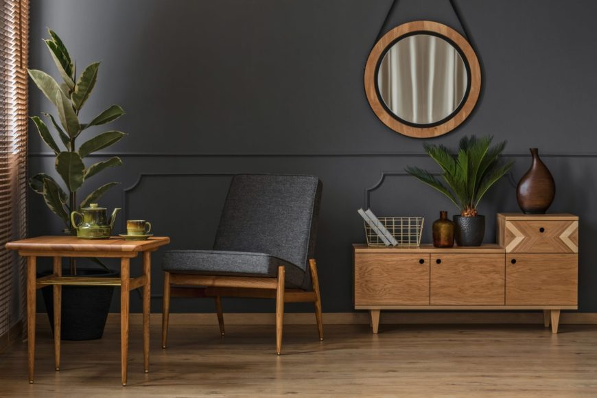 Black living room designed with a round wooden mirror above wainscoting. It has indoor plants that create a refreshing ambiance to the area.