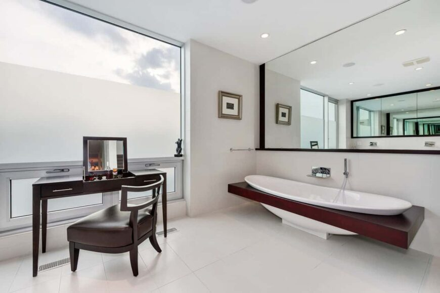 A bathtub framed with rich dark wood placed beneath a wide frameless mirror. Across it is a vanity with foldable mirror paired with a cushioned chair.