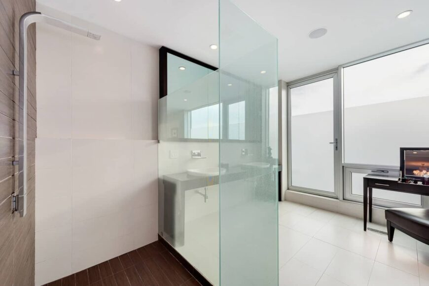 A primary bathroom with hardwood shower area and dual sink washstand paired with rectangular mirror over white tiled flooring.