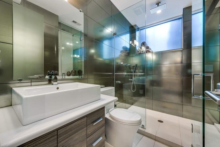 Sleek primary bathroom with a vessel sink vanity and a toilet next to it. It also includes a walk-in shower area with frosted glass windows.