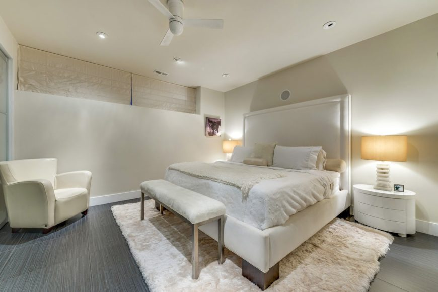 Lovely cream primary bedroom with an upholstered bed and accent chair. It has a bench at the bed's foot complementing the bedding and shaggy rug.