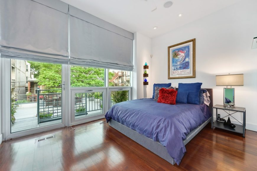 Master bedroom features a rich hardwood flooring and glass windows and door. It has a blue bed paired with dark gray nightstand.