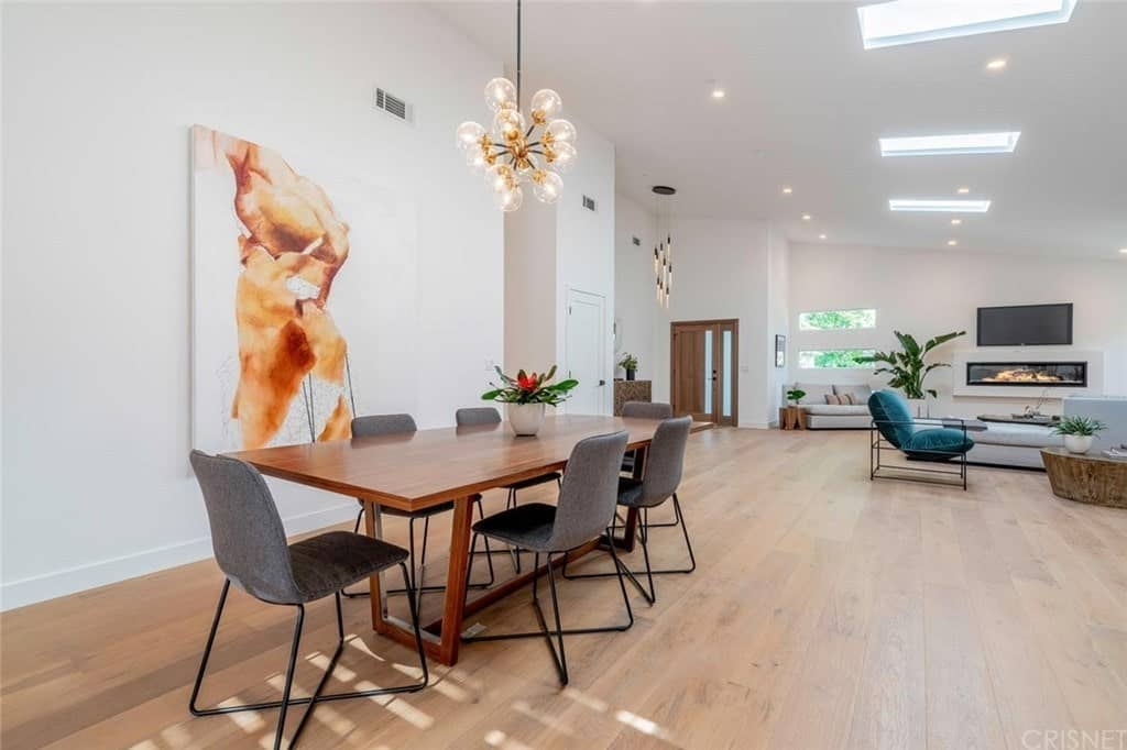 Contemporary dining room with a rectangular dining table for six under a pendant lighting and a large wall decor.