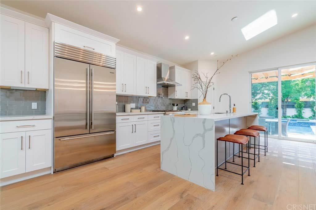 Single-wall contemporary kitchen with stainless steel appliances, gray subway tile backsplash, and an eat-it island.