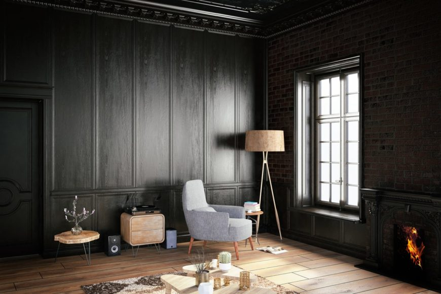 Dark living room with black full wainscoting and brick walls. It includes a gray chair lighted by a floor lamp over wood plank flooring.