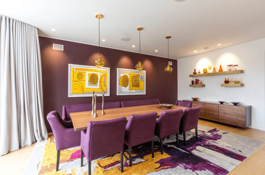 A colorful dining area in purple and yellow tones, with long rectangular wooden table, purple upholstered chairs, floating shelves, and three yellow pendant lights.
