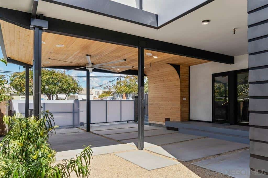 View of the covered walkway leading to the front door of a contemporary industrial home in San Diego.