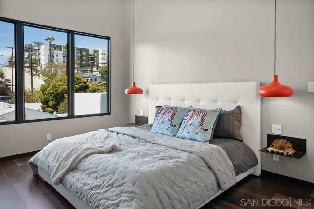 Contemporary master bedroom accented with vibrant orange pendants. It has glass windows overlooking the outdoor scenery.