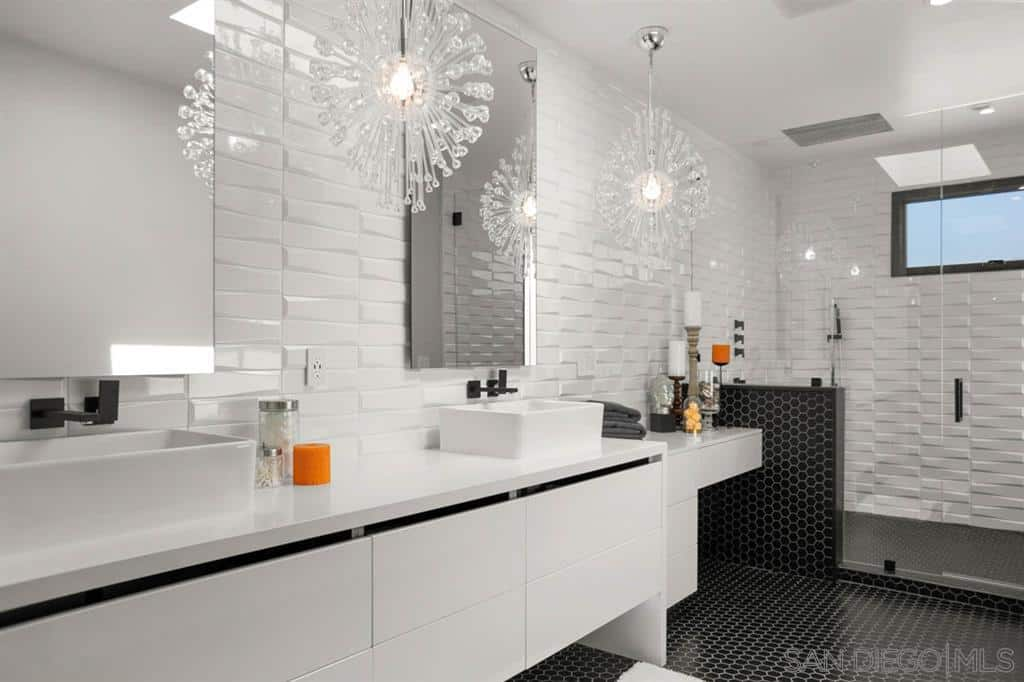 Gorgeous white primary bathroom accented with black hex tiles flooring and brick tiles walls. It is illuminated by lovely crystal snowflake chandelier.