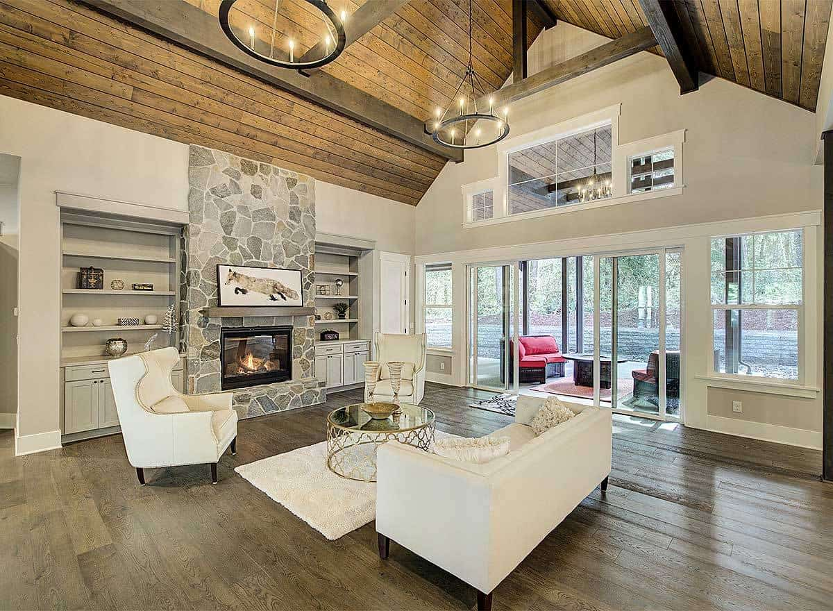 The charming dark hardwood flooring of this living room contrasts the bright beige cushioned sofa and its matching arm chairs. These also match the beige area rug underneath the round glass-top coffee table across from the stone fireplace.