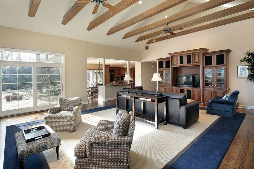 An expansive craftsman living room featuring a vaulted ceiling with exposed wood beams and cream carpet with a velvet blue border that matches the armchair over a hardwood flooring.