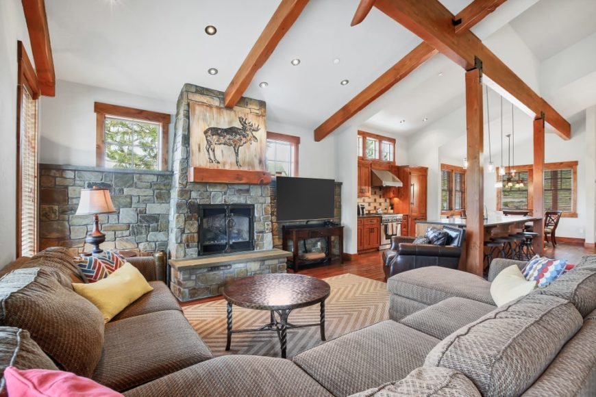 Craftsman living room accented by exposed wood beams that match the hardwood flooring and window frames. It has an L-shaped sectional sofa that faces the fireplace mounted on stone wall and pillar.