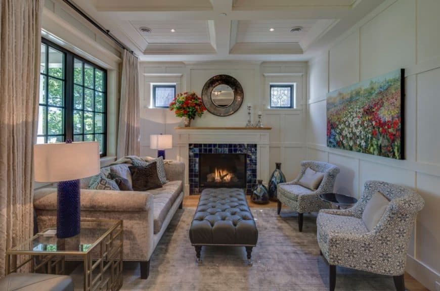 A round mirror placed above a blue brick fireplace creates a dramatic focal point in this craftsman living room. It has white panelled walls complementing the white coffered ceiling.
