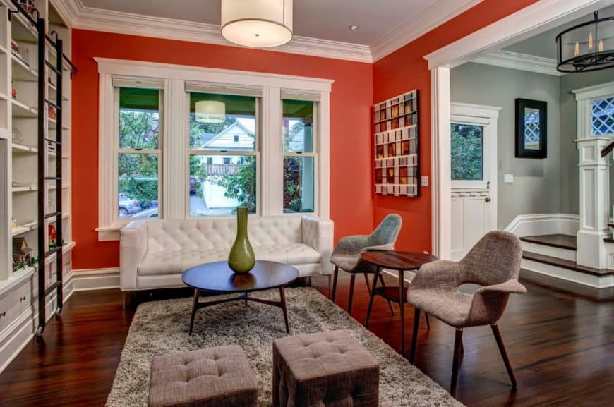 Vibrant red living room features white built-in bookshelves facing the white tufted sofa and brown chairs and stools. A wooden coffee table sits in the middle over a brown shaggy rug.