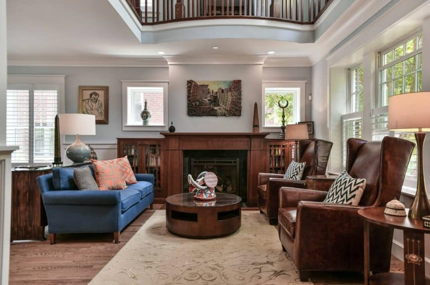 Fresh and light living room accented with blue couch paired with a round wooden table and brown leather high back chairs.