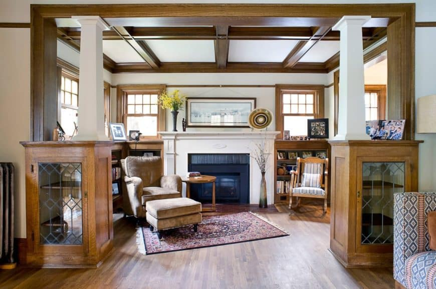 Craftsman living room features a brown velvet recliner that sits on a vintage rug with a wooden round side table beside the fireplace. It also has a hardwood floor along with a coffered wood ceiling.