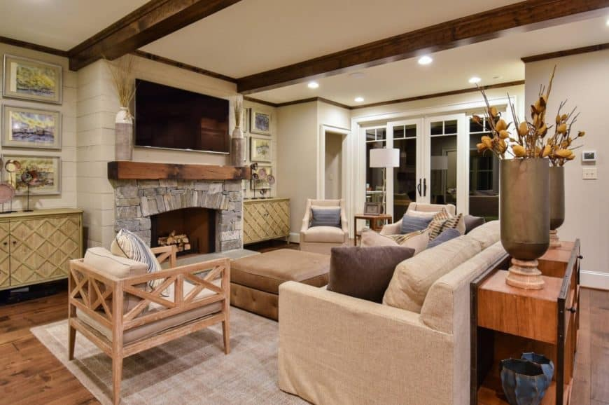 Gorgeous living room featuring a stone fireplace lined with a rustic wood that matches the exposed wood beams on the ceiling. It is fixed on a shiplap wall between wooden cabinets styled with frames and decors.