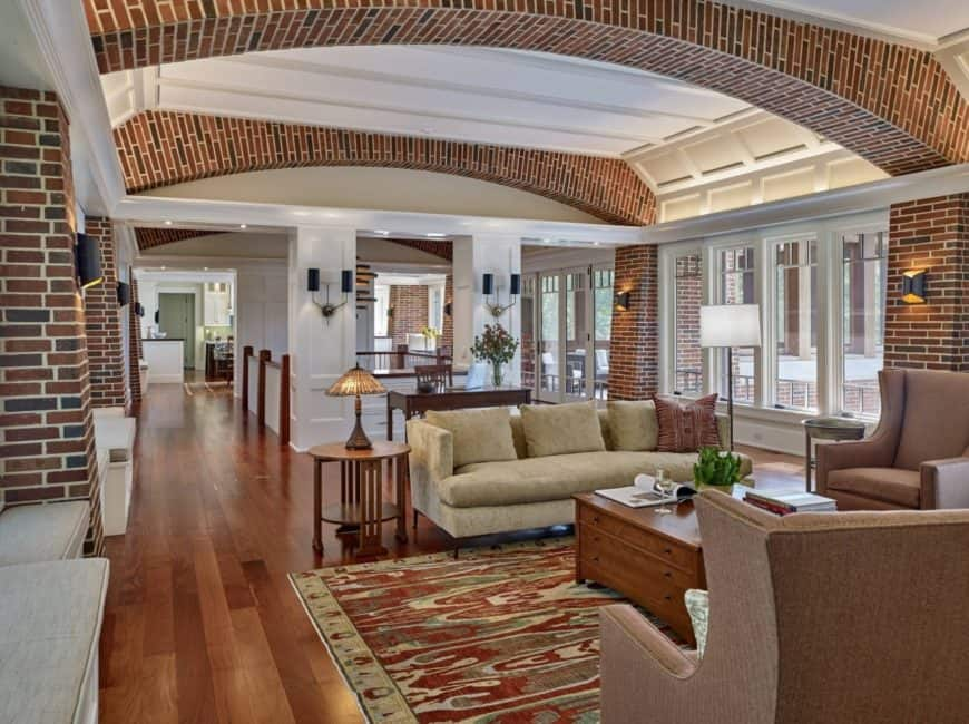 Magnificent living room accented with brick arches on the ceiling and pillars lighted by black wall sconces. It has a wooden center table surrounded with an upholstered sofa and brown wingback armchairs.