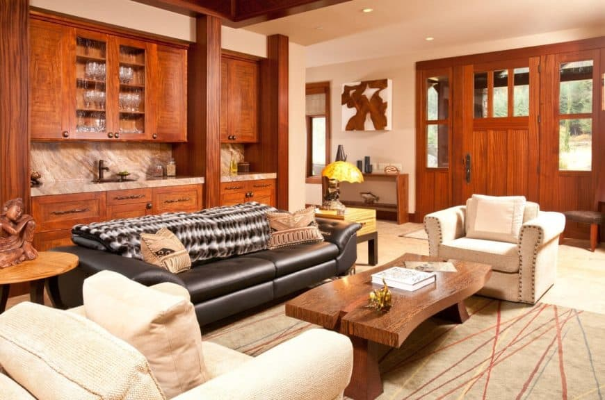 Warm living room with black leather sofa paired with white upholstered chairs and a wooden coffee table. They sit on a line patterned rug over a hardwood flooring.