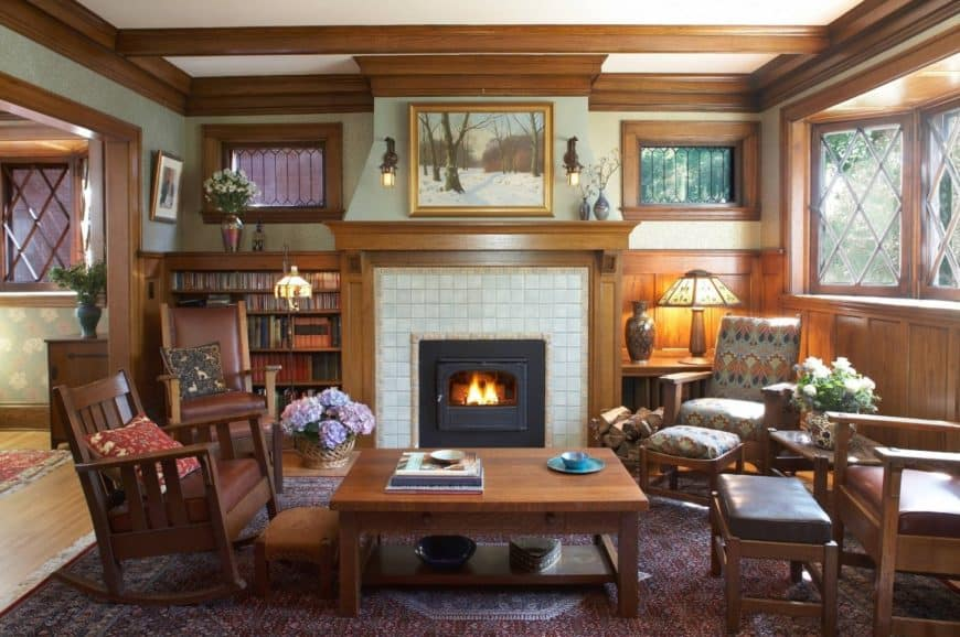 Craftsman living room with a built-in bookshelf next to the fireplace mounted to a white tiled wall. It has wooden chairs and stools paired with a wooden center table.