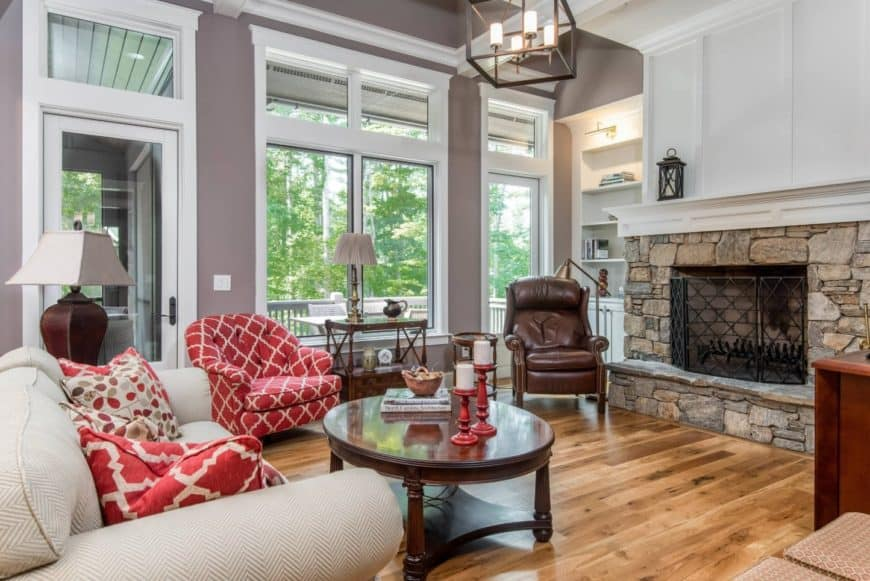 Gorgeous living room with a pop of red from the upholstered chair, throw pillows and candle holders. It features a high ceiling with a hanging cube chandelier.