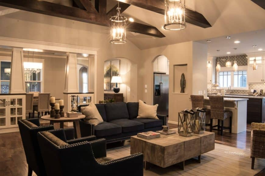 Craftsman living room features a rustic wood coffee table paired with a black sofa set. It is illuminated by cylindrical chandeliers that hung from a vaulted ceiling with exposed wood beams.