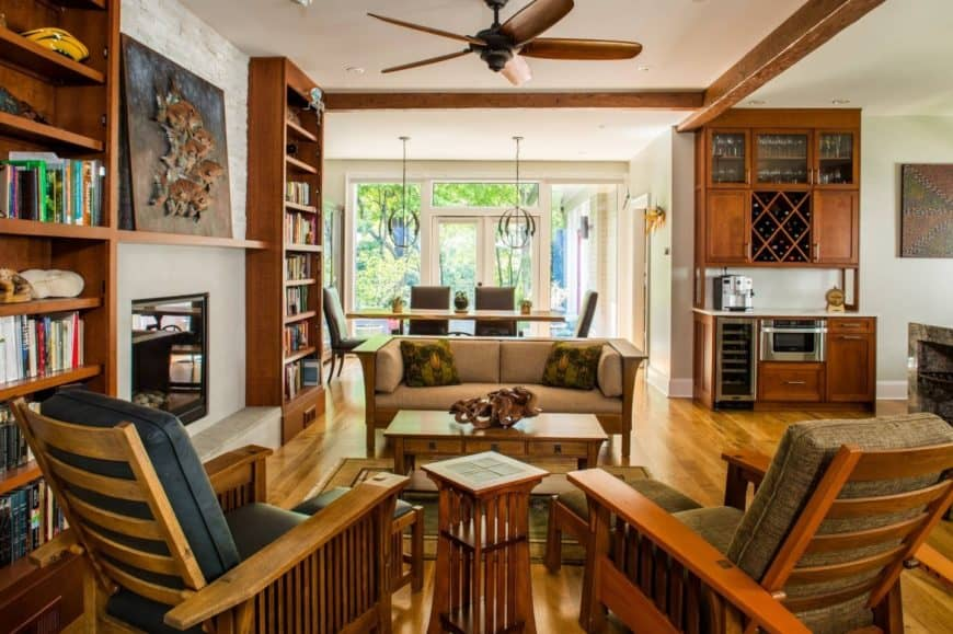 Craftsman living room features built-in bookshelves along with mismatched sofa and chairs paired with wooden center and side tables.