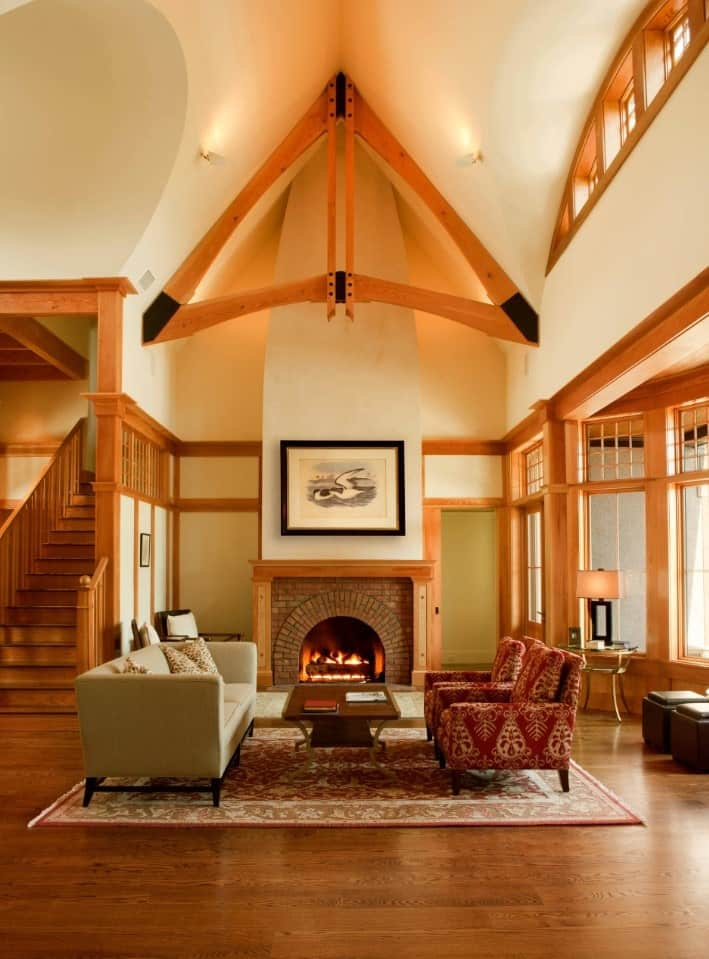 Craftsman living room accented by a triangular wooden beam on a high, vaulted ceiling. It features mismatched sofas over a red vintage rug facing the brick fireplace that warms the room.