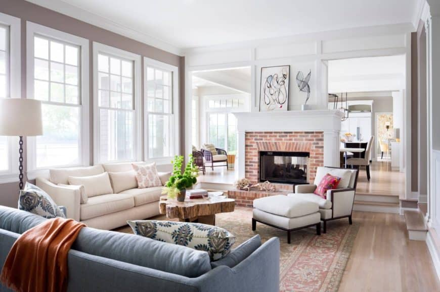 Bright living room with glass windows, white and blue sectionals, brick fireplace and a tree trunk handmade coffee table that sits on a red vintage rug over hardwood flooring.