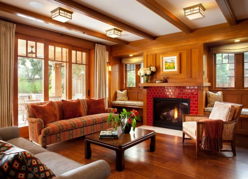 Formal craftsman living room offers cozy seats over a hardwood flooring along with a modern red brick fireplace.