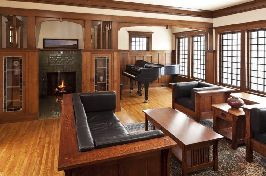 Craftsman living room features a wooden sofa set fitted with black leather that complements the baby grand piano in the corner.