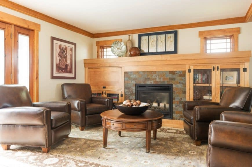 Brown leather chairs surrounded the wooden center table that faces the fireplace in this small living room. The whole area is covered by a green vintage rug.