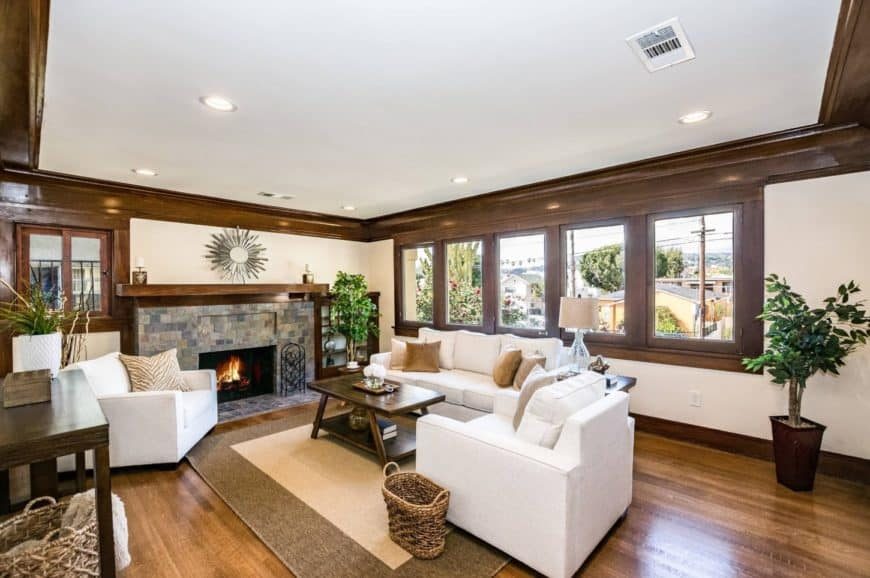 Craftsman living room styled with a silver sunburst mirror atop a stone fireplace and indoor plants that give life to the room. It also features white sectional sofa set paired with a wooden coffee table.