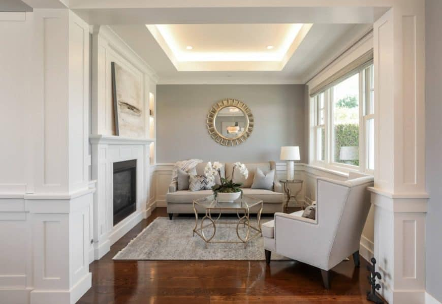 Clean white living room features a gray accent wall against wainscoted white walls mounted with a round mirror that complements the glass center table.