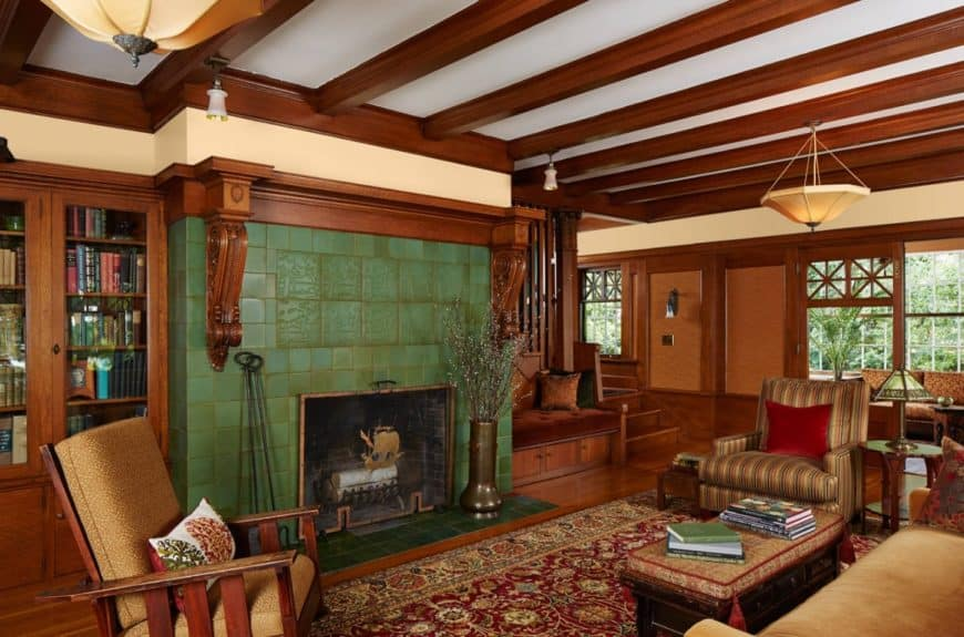 A green brick fireplace stands out in this wooden living room. It features exposed wood beams ceiling with hanging pendant lights along with a wooden sofa set sitting on a red vintage rug.