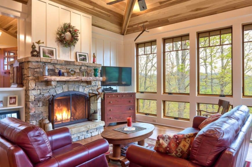Craftsman living room with red leather sofa set paired with a wooden coffee table faces the stone fireplace. It has vaulted wood ceiling and glass windows overlooking a spectacular mountain view.