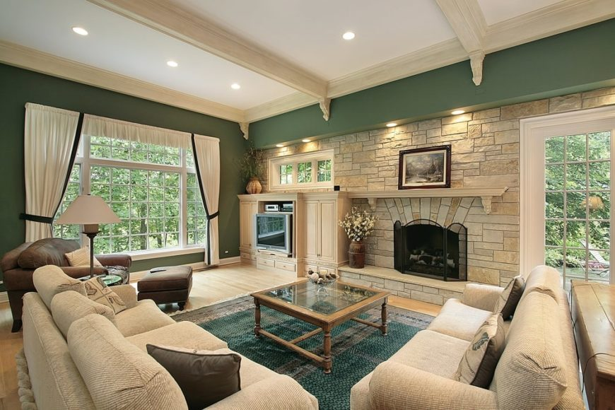 Fresh, green living room features a stone wall that complements the light hardwood floor along with gray sectionals that sit on a green rug.