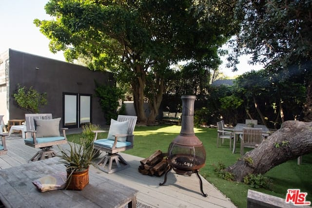 A light wooden deck with charming wooden furnitures that complement the relaxing feels of the backyard. Spacious lawn surrounded by plants and huge beautiful trees creates tranquility and peaceful vibes.