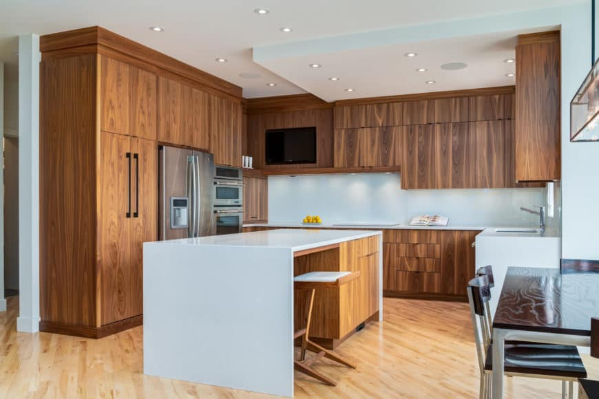 Sophisticated kitchen with natural wood cabinetry and a white marble breakfast island that matches the countertops.
